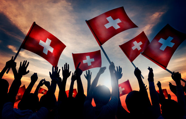Silhouettes of People Holding Flag of Switzerland